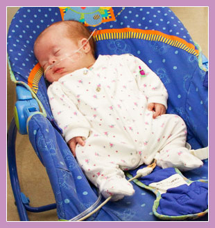 Photo of a premature child asleep in a baby seat.
