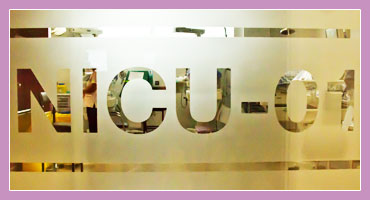 Close up photo of door into NICU at Holles Street Hospital. Transluscent glass features text 'NICU-01'